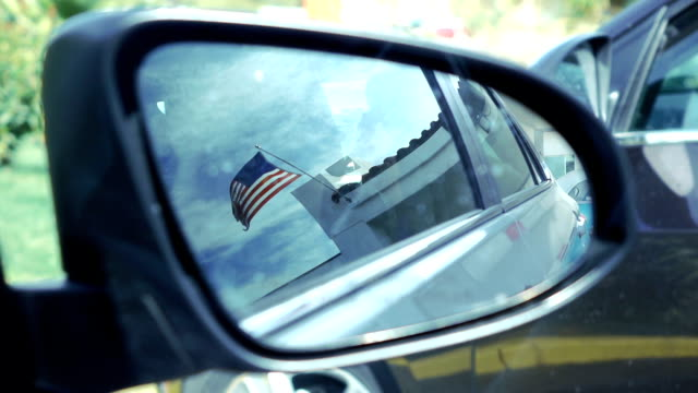 reflection of a american flag in a car mirror in slow motion 120fps - bandiera nazionale video stock e b–roll