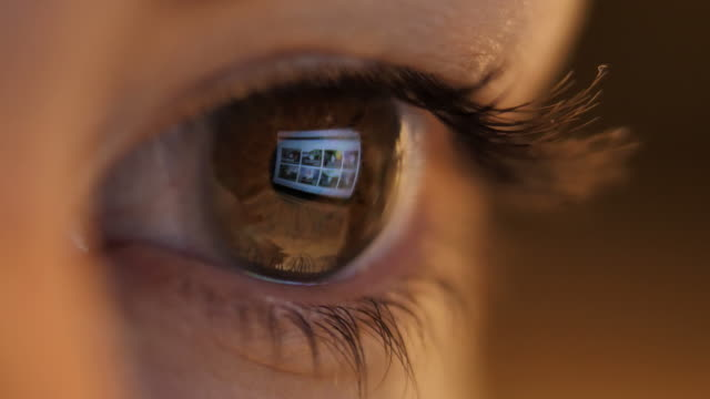 reflection of a laptop in a woman's eye, woman working on a laptop, macro shot video