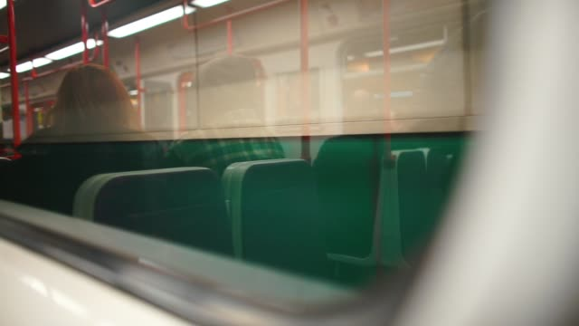 Reflection of a woman in a medical mask in a subway train.