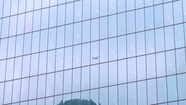 Reflection of airplane flight on the glass building in 4k slow motion 60fps
