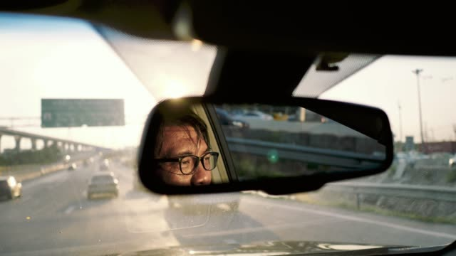Reflection of asian man face in rear-view mirror in moving car, traffic Asian senior man in a mirror while driving car on a busy road in a city. Bangkok, Thailand. rear view mirror stock videos & royalty-free footage
