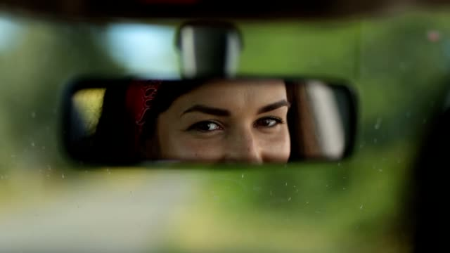 reflection of cute woman in car rearview mirror - woman mirror video stock e b–roll