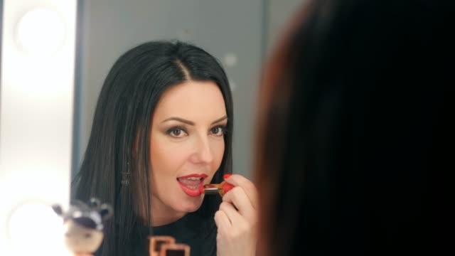 reflexion der dame, die ihr make-up auftragen. brünette reife frau setzen lippenstift beim blick in den spiegel. make-up in der nacht immer vor dem schlafengehen zum feiern bereit. slow-motion - lippenstift stock-videos und b-roll-filmmaterial