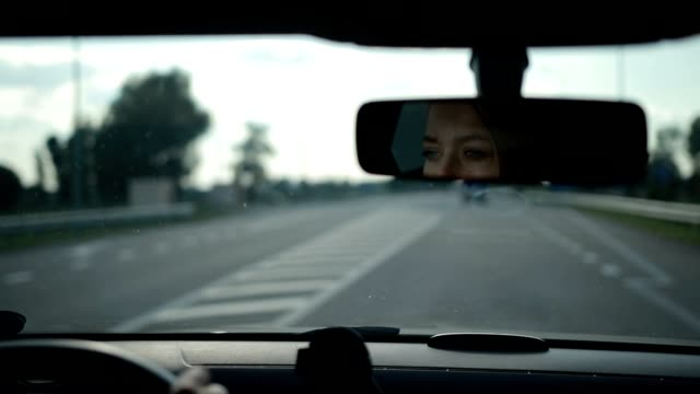 Reflection of lovely woman in car rear-view mirror Reflection of charming blond female driver with amazing blue eyes in car rear-view mirror while driving vehicle on highway. Young woman driving car on freeway and looking at rear-view mirror. rear view mirror stock videos & royalty-free footage