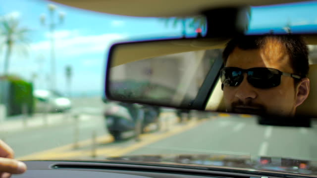 Reflection of male face in sunglasses in rear-view mirror in moving car, traffic Reflection of male face in sunglasses in rear-view mirror in moving car, traffic rear view mirror stock videos & royalty-free footage