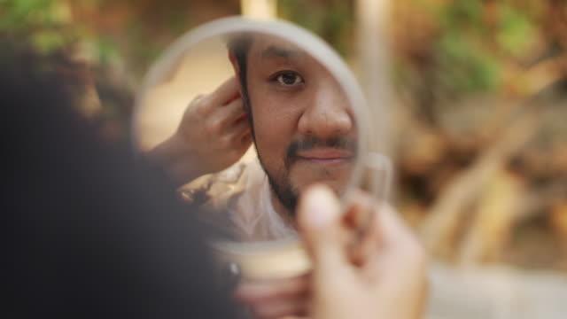 vídeos de stock e filmes b-roll de reflection of man face in small mirror getting hair cut at home - covid hair