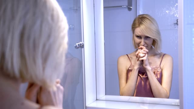 reflection of sad woman crying near the mirror - comparsa video stock e b–roll
