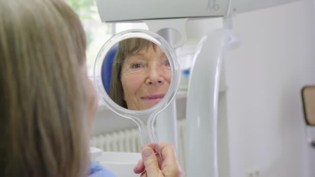 Reflection of senior woman holding hand mirror