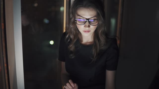 reflection of the screen with glasses. girl uses a smartphone in the dark. portrait of a young woman on the background of the night city