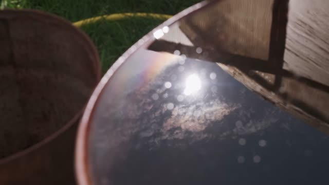 Reflection of the sun and clouds in a water tank. Reflection of the sky in a water tank on an agricultural plot. Against the background of an empty tank, grass and a water hose. The reflection shows the sun and clouds. midday stock videos & royalty-free footage