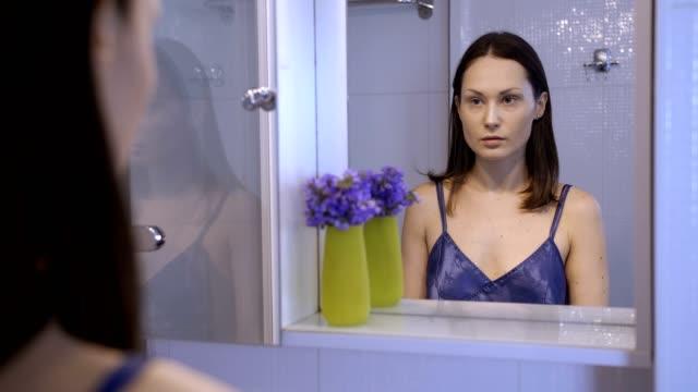 reflection of unhappy pretty woman in mirror - comparsa video stock e b–roll