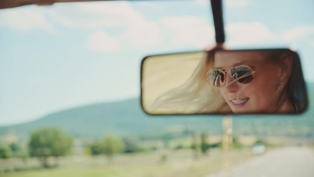 Reflection of woman traveling in van Young woman reflecting on rear-view mirror of van. Female is talking while traveling in vehicle during vacation. She is wearing sunglasses. rear view mirror stock videos & royalty-free footage