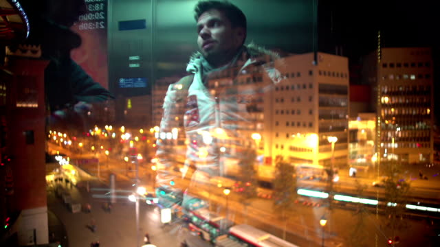 Reflection of young men using glass elevator at shopping mall, night city life video
