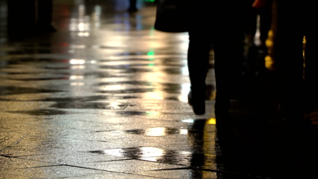 Reflection silhouettes of unrecognizable people on wet pavement in streetlights. Long shadows. Rainy evening in city street with street lights, shiny asphalt from rain. Unrecognizable pedestrians, young people. Night city rain. Concept of shopping video
