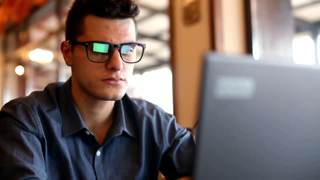 Reflections of laptop monitor screen in man's glasses. Portrait of young caucasian freelancer businessman working and browsing internet in office. Hacker at work stealing accounts database