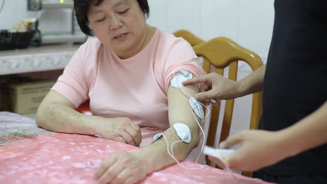 Reflexology A Chinese female adult is experiencing TENS (Transcutaneous Electrical Nerve Stimulation), assisted by her family member at home. electrode stock videos & royalty-free footage