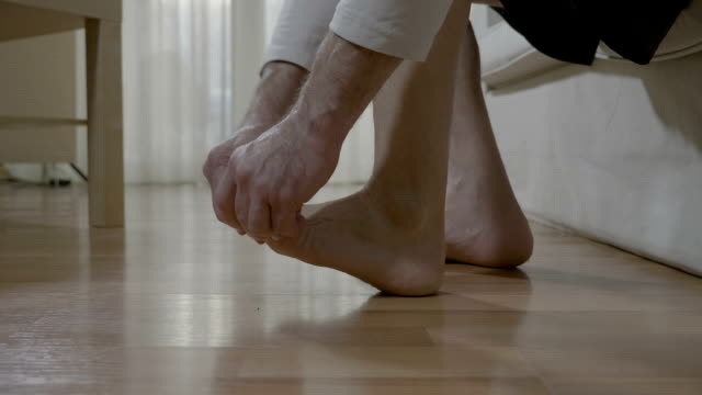 reflexotherapy massage at home of elderly man with rheumatic illness relieving himself the stiffness and ache of the of the foot and toes - dito del piede video stock e b–roll