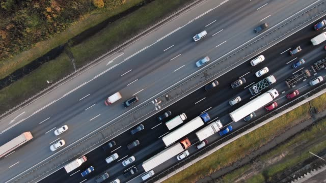 refreshed multi-lane highway with trucks crossing wide field - vídeo