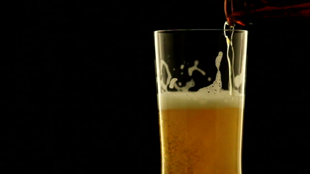 Refreshing beer into rotate glass in the dark night video