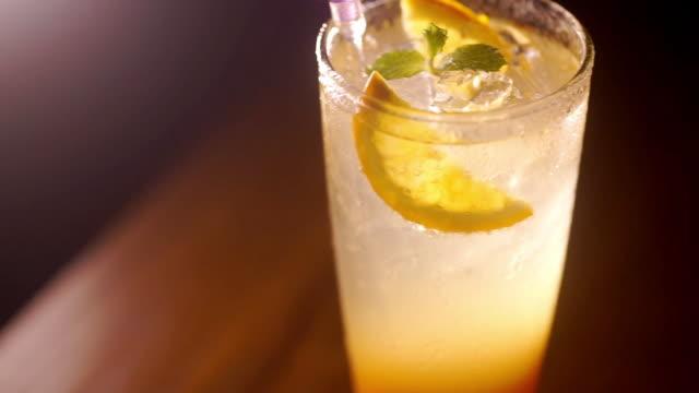 erfrischender cocktail mit limettensaft in glas auf dunklem hintergrund. - tropischer cocktail stock-videos und b-roll-filmmaterial