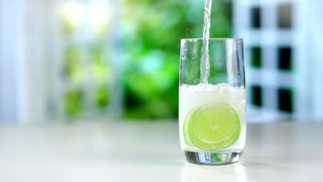 A refreshing drink being poured into a glass with ice, lemon and lime A refreshing drink being poured into a glass with ice, lemon and lime. tonic water stock videos & royalty-free footage