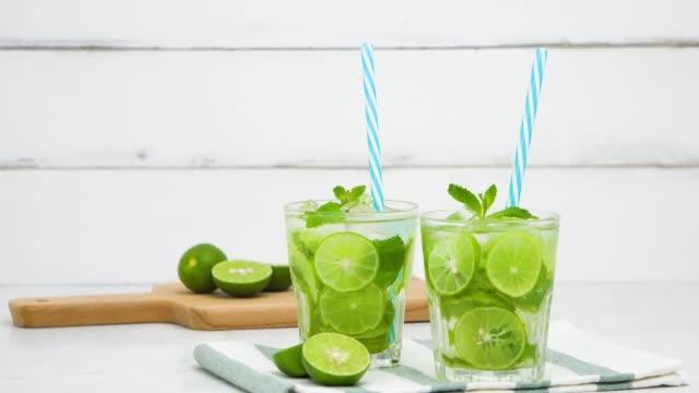 erfrischenden mojito cocktail trinkt in den gläsern - tropischer cocktail stock-videos und b-roll-filmmaterial
