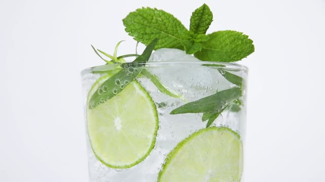 refreshing summer cocktail lemonade with ice, tarragon, lime, mint, bubbles move in glass close up