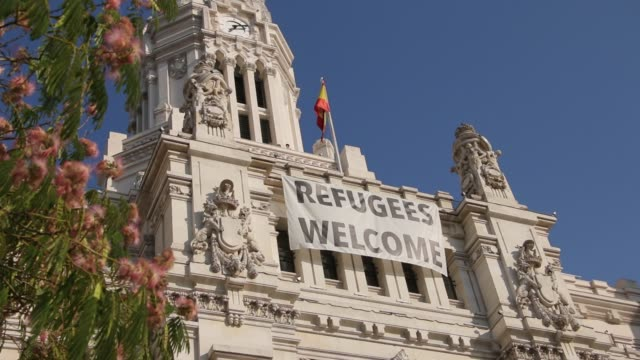 refugee welcome flag on the facade of palacio de comunicaciones in madrid - fuggitivo video stock e b–roll