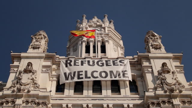 Refugee welcome poster on the facade of Palacio de comunicaciones in Madrid Refugee welcome banner in the center of Madrid, Plaza Cibeles, Spain syria stock videos & royalty-free footage