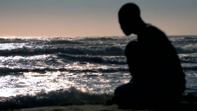 Refugees,migration,human rights.silhouette of sad black man alone at the beach