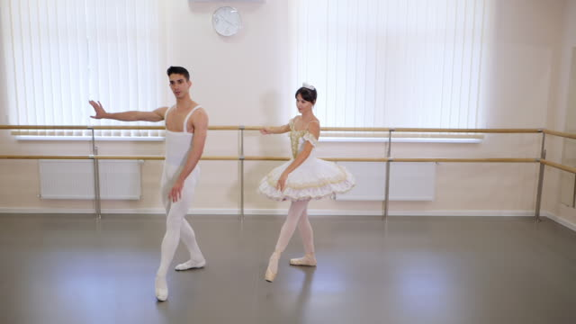 Rehearsal in the ballet hall or studio with minimalism interior. Young professional sensual dancer's couple in beautiful costumes dancing together. Slow motion