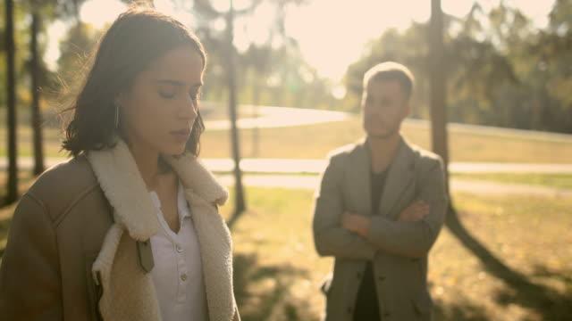 relationship problems,young couple,autumn park - cisza filmów i materiałów b-roll
