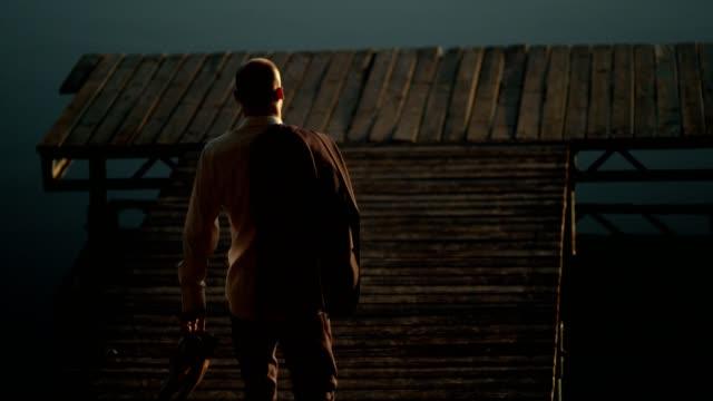 vídeos de stock e filmes b-roll de relax after work. businessman admiring lake sunset - man admires forest