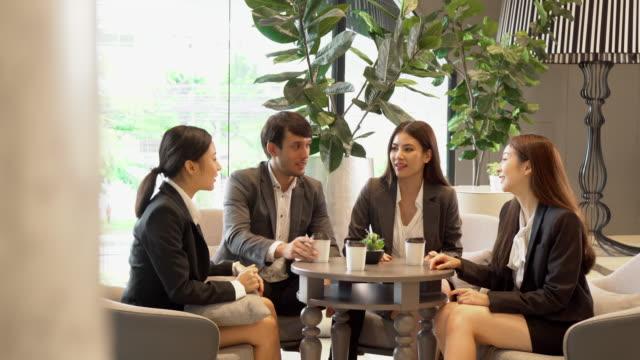 rilassati gruppo di uomini d'affari asiatici che bevono caffè e discutono in ufficio - pranzo video stock e b–roll