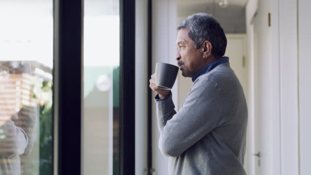 Relax, retirement is finally here 4k video footage for a senior man drinking coffee and looking thoughtfully out of a window medicare stock videos & royalty-free footage