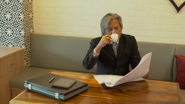 4K Relax Senior BusinessMan is Read newspaper and coffee break in co-working space.