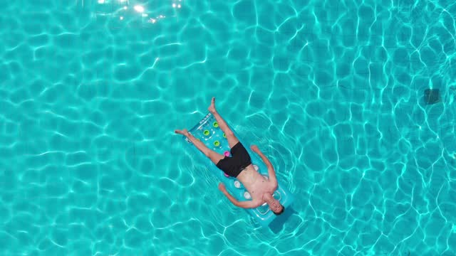relax, summer-young man sunbathing on the mattress in the pool - drone relax, summer-young man sunbathing on the mattress in the pool - drone sunbathing stock videos & royalty-free footage