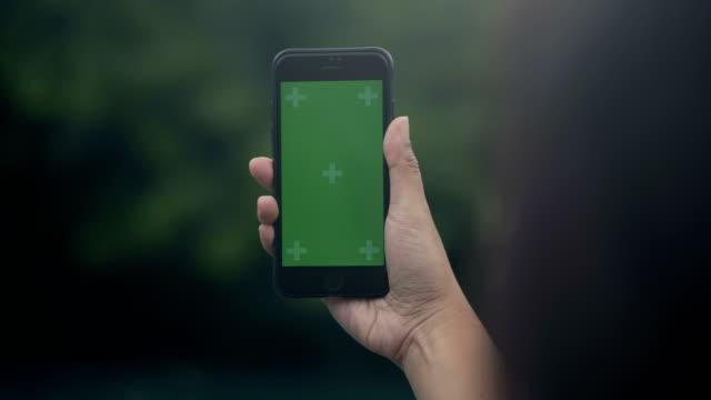공원에서 휴식: 스마트 전화 녹색 화면 - hand holding phone 스톡 비디오 및 b-롤 화면