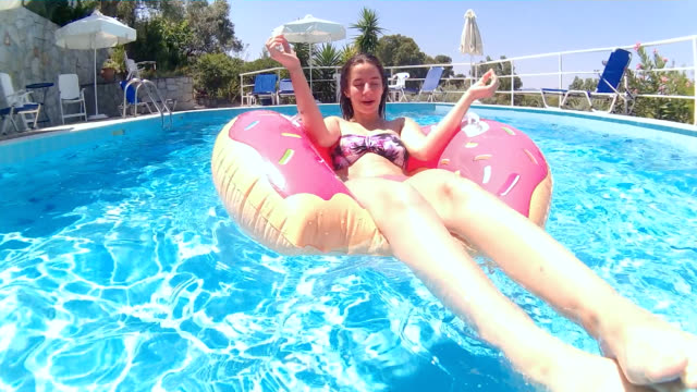 Relaxation on inflatable ring in swimming pool video