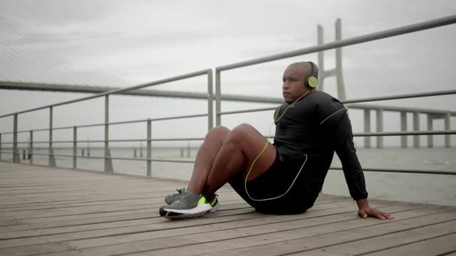 entspannte afroamerikanische mann im kopfhörer auf hölzerne pier. - sportchampion stock-videos und b-roll-filmmaterial