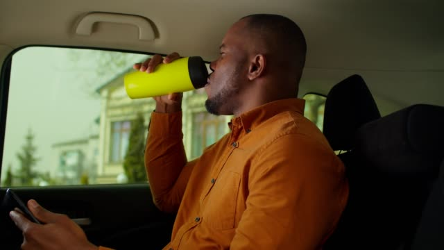 Relaxed african man riding in backseat of taxi cab
