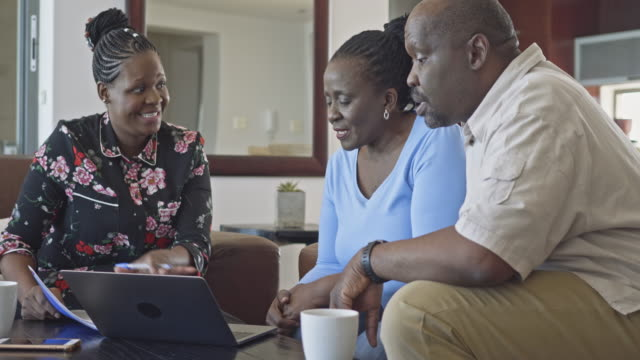vídeos de stock e filmes b-roll de relaxed african mature couple at home with financial advisor - 55 59 anos