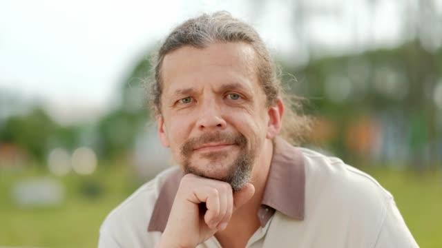 stockvideo's en b-roll-footage met een ontspannen aantrekkelijke man van middelbare leeftijd met lange grijze haren kijkt in de camera, glimlacht en lacht. - portait background