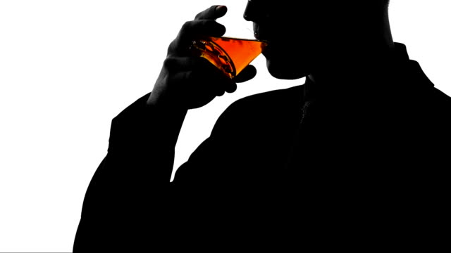 Relaxed businessman drinking cognac after workday, enjoying taste of beverage video