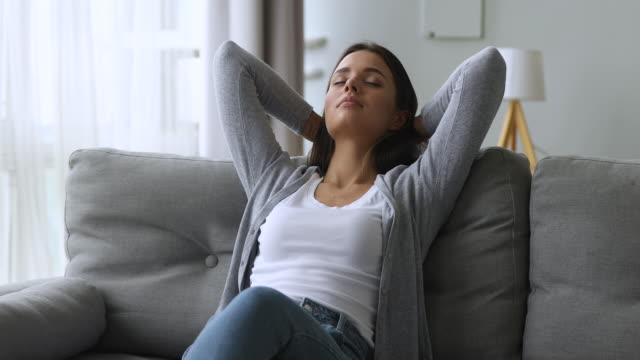 vídeos y material grabado en eventos de stock de relajado tranquilo hermosa chica apoyada en sofá soñando disfrutando del bienestar - cómodo conceptos