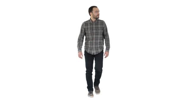 entspannter, lässiger mann in jeans und hemd zu fuß und mit blick auf die seiten auf weißem hintergrund - mann bart freisteller stock-videos und b-roll-filmmaterial