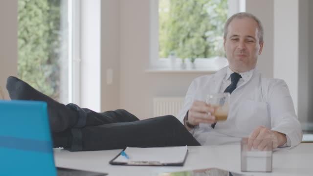 편안한 백인 의사는 테이블에 다리를 앉아 커피를 마시는. 병원에서 휴식을 취하고 미소를 지으며 의사 유니폼을 입은 평온한 남자의 초상화. 직무 만족도. 시네마 4k 프로레스 본사. - 한 명의 중년 남자만 스톡 비디오 및 b-롤 화면
