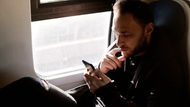 Relaxed comfortable Caucasian freelance worker texting on smartphone messenger app enjoying comfortable train ride