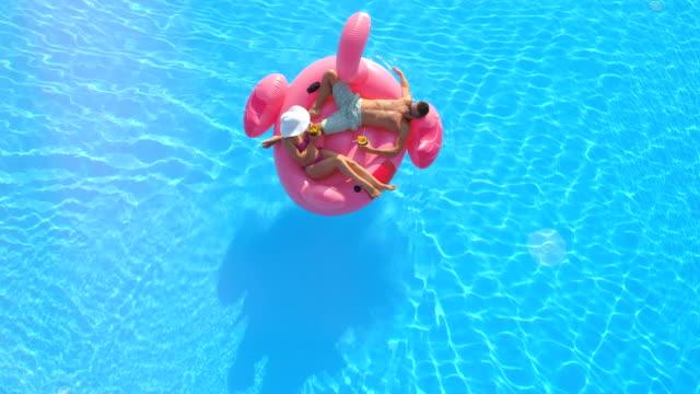 vídeos de stock, filmes e b-roll de antena lens flare: casal descontraído beber cocktails na perna de flamingo rosa - inflável