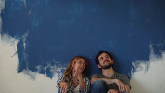 Relaxed couple taking a break from their home improvement project talking and pointing at the ceiling